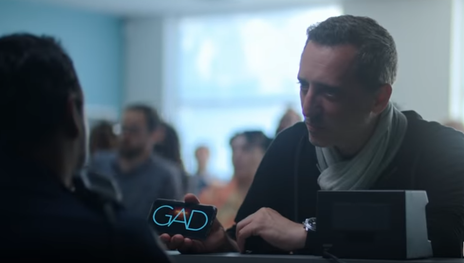 Gad Elmaleh holding a mobile phone that says GAD