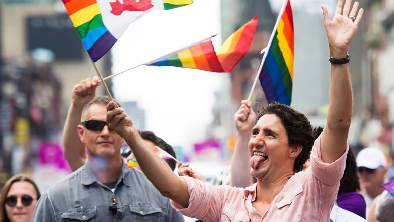 A man waving a gay pride flag in Canada